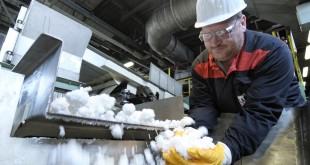 Rubber production at LANXESS's Dormagen site. An employee monitors rubber flakes, which are later compressed into bales, primarily for use in the tire industry.